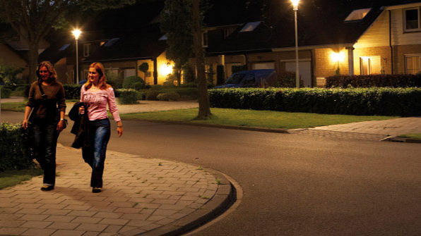 Two women are walking in a street illuminated with Philips white light