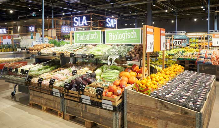 A well-stocked fresh fruit and vegetables section of an Albert Heijn supermarket.