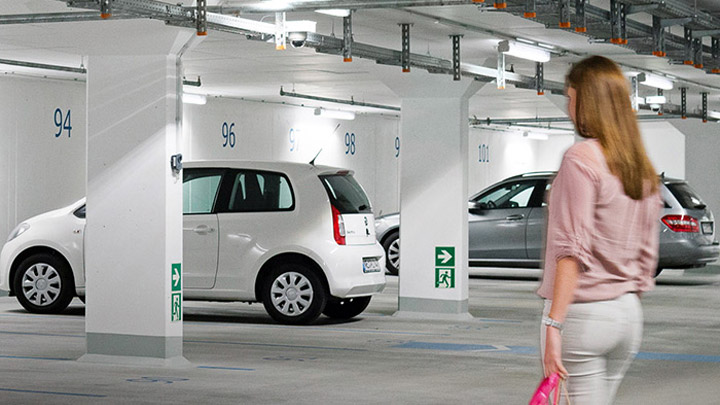 Woman in a carpark with GreenParking system - safety lights with savings