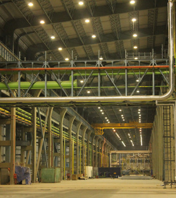 Highbay luminares installed across very high ceiling processing and manufacturing areas within the plant